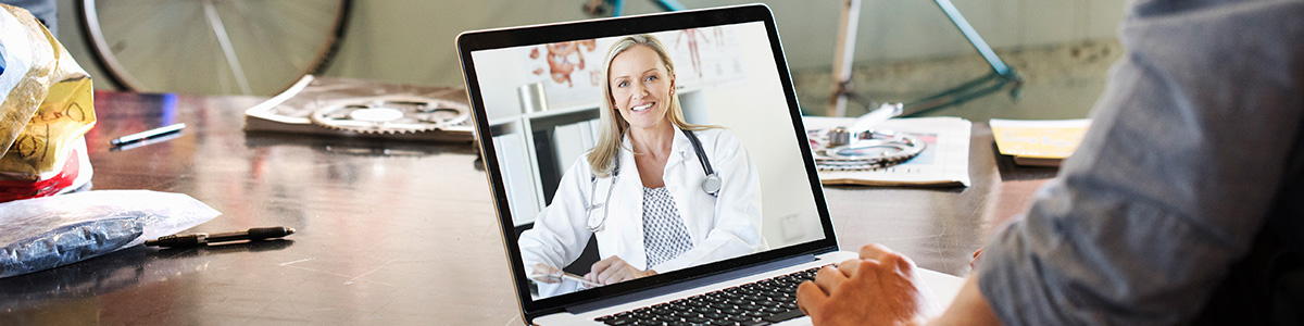 Patient using telemedicine serves from their laptop.