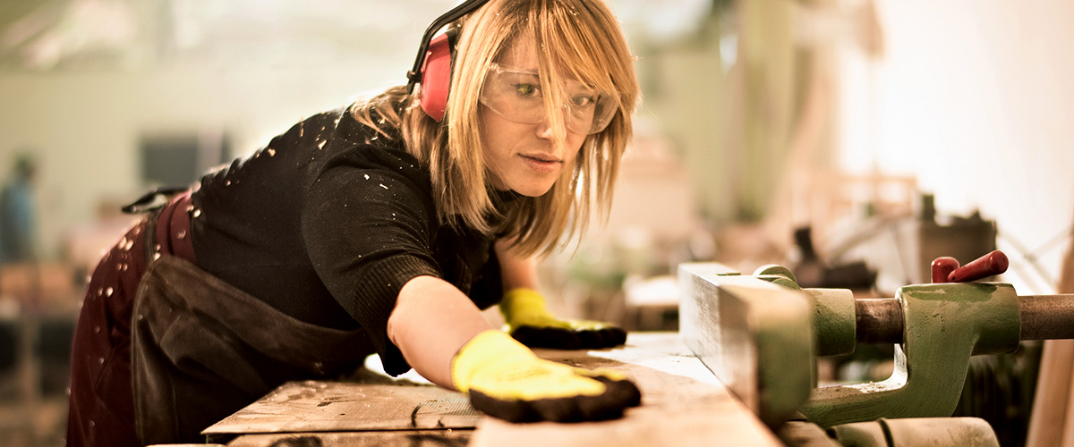 Female carpenter working on a piece of wood.