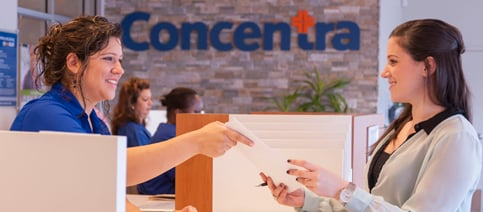 Checking Into Urgent Care Woman at Counter