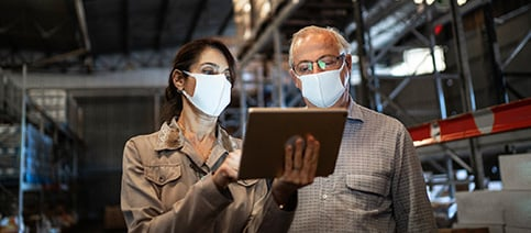 Two employers wearing face masks discussing healthcare needs.