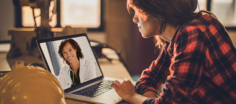 Female speaking to a doctor through her laptop via telemedicine.