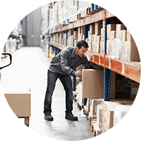 Man in warehouse putting up boxes keeping ergonomically friendly