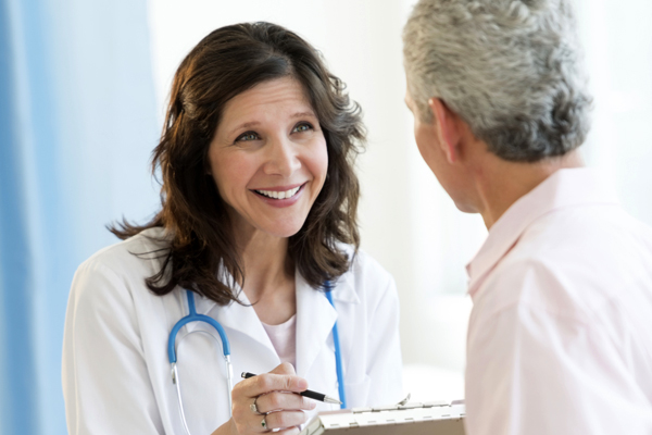 Woman Doctor Smiling At Patient