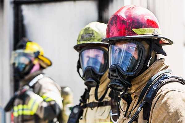 Firefighters wearing masks to protect from the smoke.