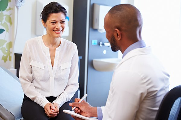 Savings for Patient Woman Smiling Talking to Doctor
