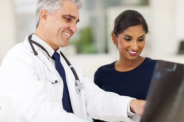 Specialized Benefits For Patients Doctor and Patient Smiling at Screen