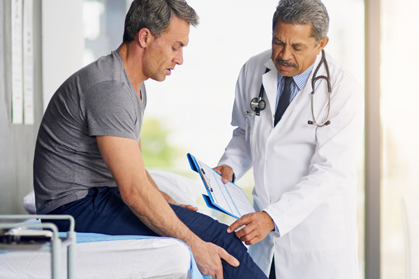 Urgent Care Doctor Examining Man's Knee