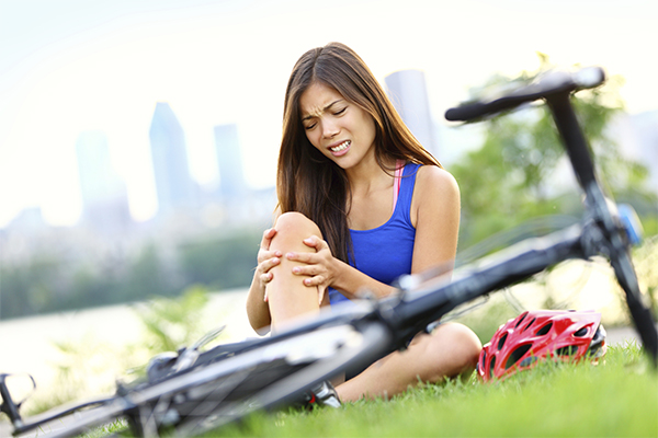 Woman Holding Knee Next to Fallen Bike
