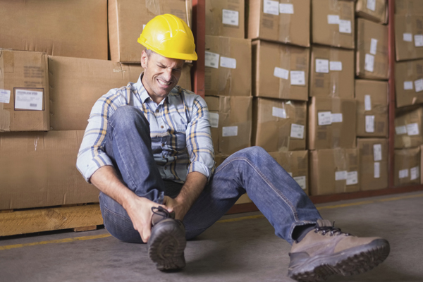 What Does Workers Compensation Cover Worker Holding Ankle