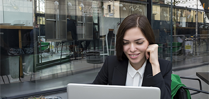 Woman in professional attire works on computer outside coffee shop