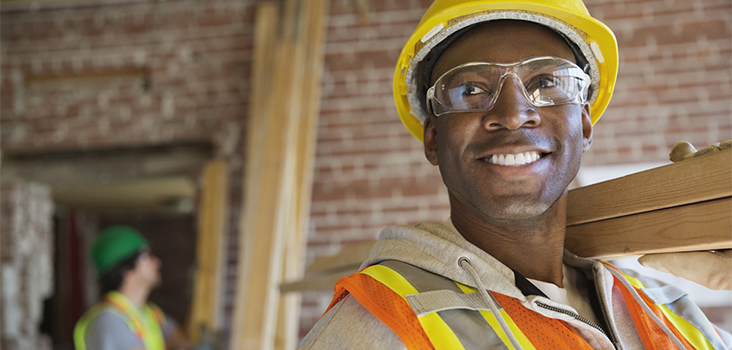 Male construction worker wearing yellow hard hat and carrying wood planks