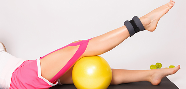 Woman exercising her knee on a small yoga ball