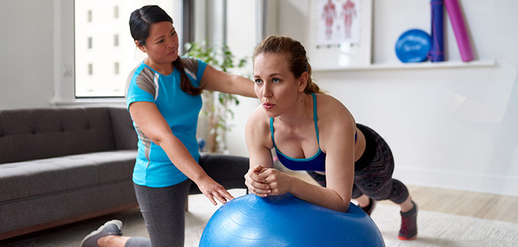 Female athletic trainer training a patient for core stability.