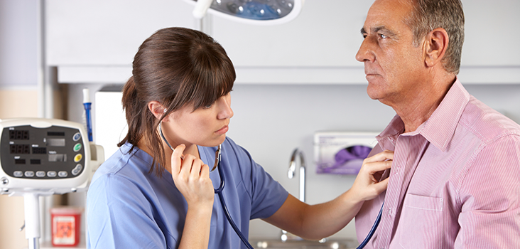 Female physician listening to male patient's heartbeat with stethoscope