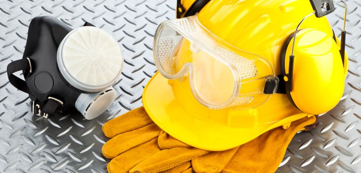 Hard hat and gloves on a metal surface