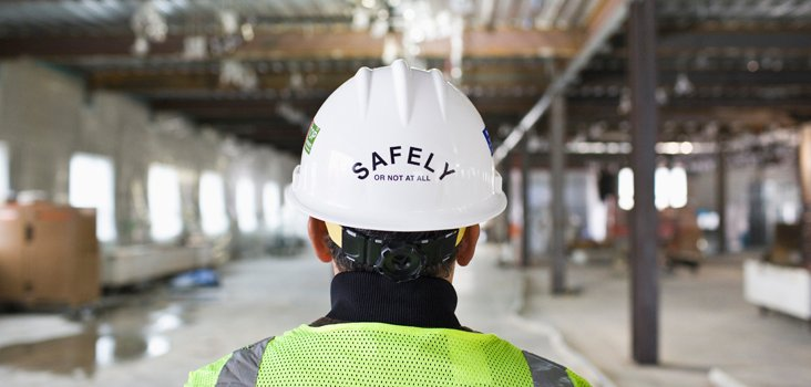 "Worker wearing a white hard hat that reads ""SAFELY or not at all"""