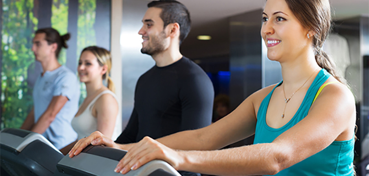Group of men and women in athletic clothing walking on treadmills