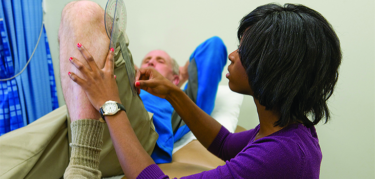 Nurse measuring the angle of an older patient's knee