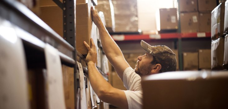 Man working in warehouse stacking boxes