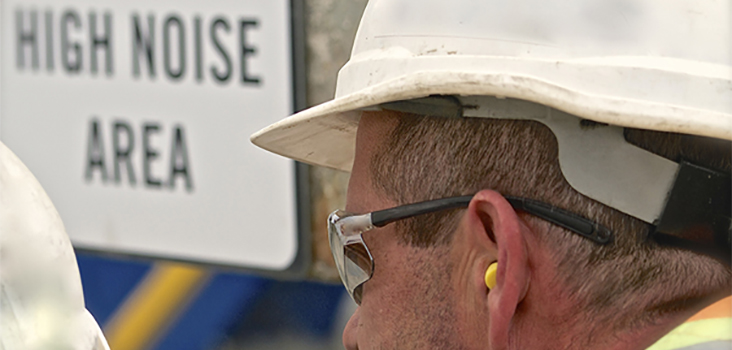 Man wearing hard hat and ear plugs in a high noise area