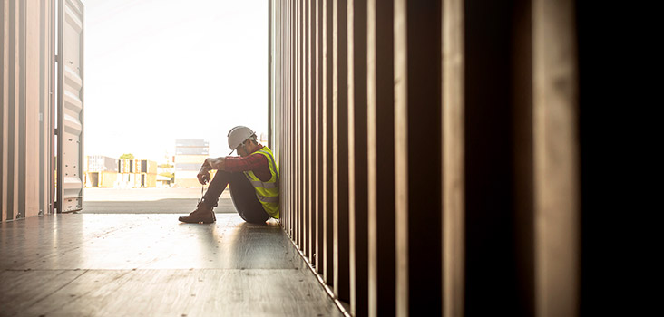 Construction worker sitting in a dim area