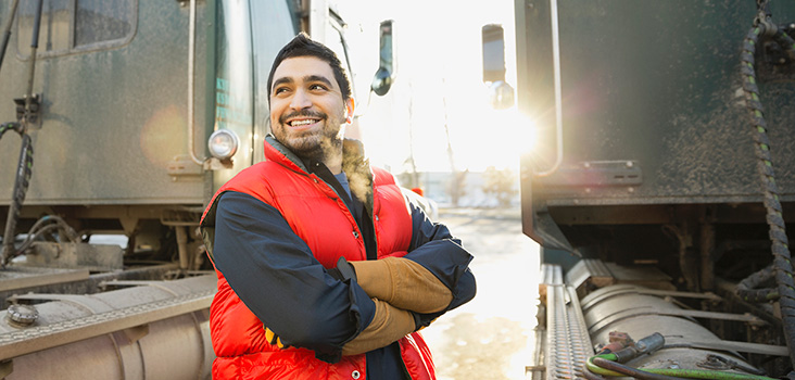 Male truck driver smiling at his semi trucks