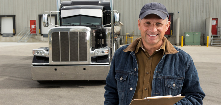 CDL certified truck driver holding a clip board in front of his truck.