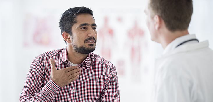 Man touching his throat speaking to male physician