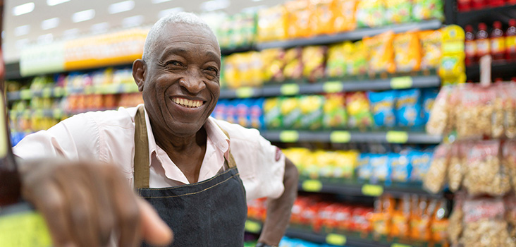 Male grocer chain worker smiling at his job.