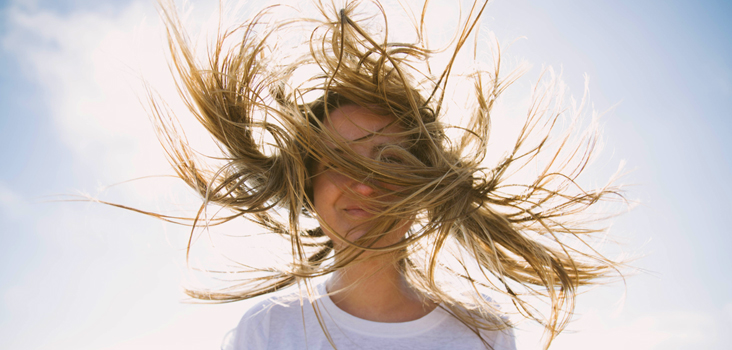Woman standing in front of the sun with her hair being blown by the wind