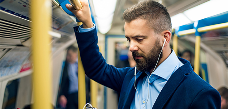 Businessman with beard wearing headphones on subway