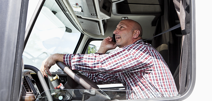 Truck driver driving semi truck and talking on phone