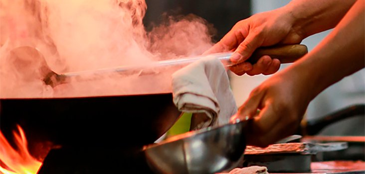 Chef works with a steaming wok under a fire