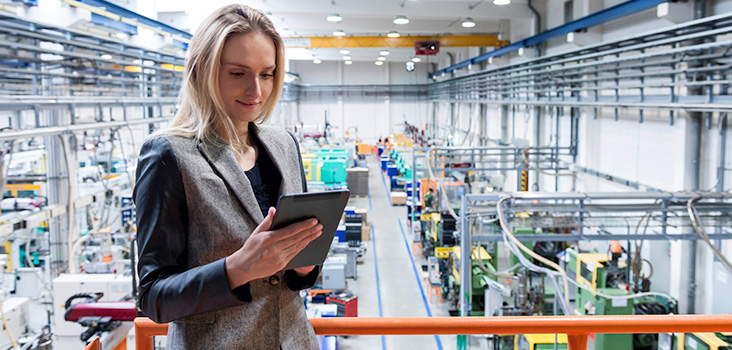 Woman holding ipad in manufacturing plant, reading manufacturing news.