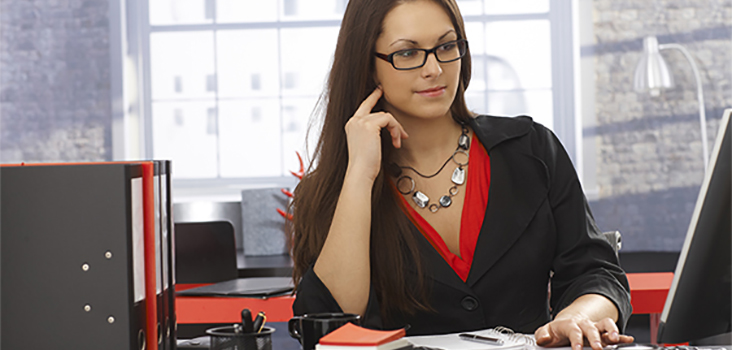 Woman in professional attire working on desktop computer