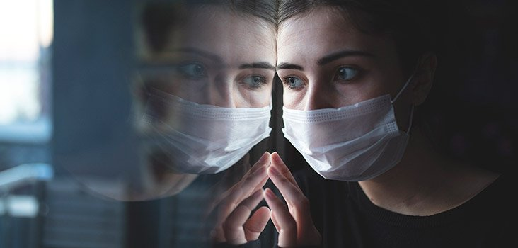 Woman wearing medical mask looks at her reflection through a glass window