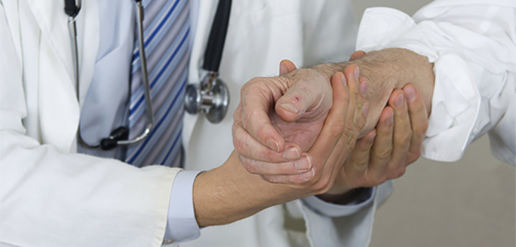 Physician checks out older man's wrist and arm