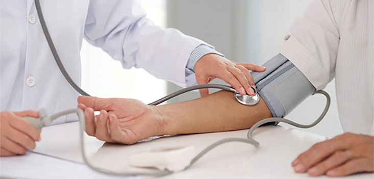 Physician with stethoscope on patient's arm with blood pressure cuff