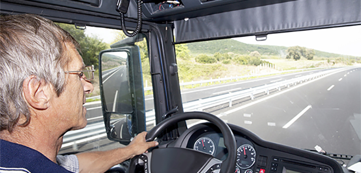 Older male truck driver driving semi-truck on road