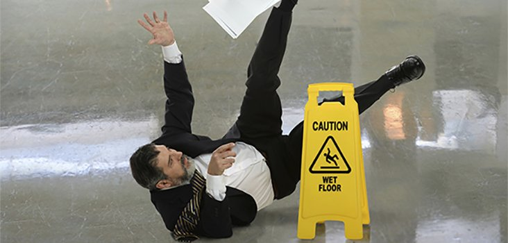 Man in professional attire slipping and falling on wet floor