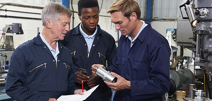 3 male engineers looking at a metal cylinder