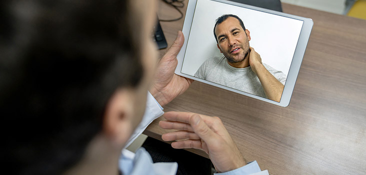 Male employee with a neck injury using telemedicine to speak to a doctor.
