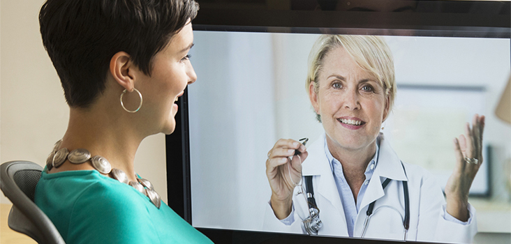Woman videochatting with physician through television