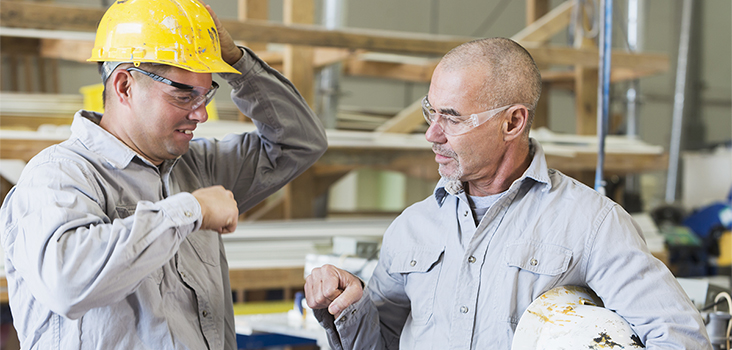 Man in yellow hard hat talking to coworker