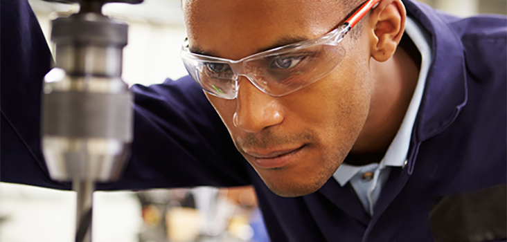 Worker wearing safety glasses looking at machine