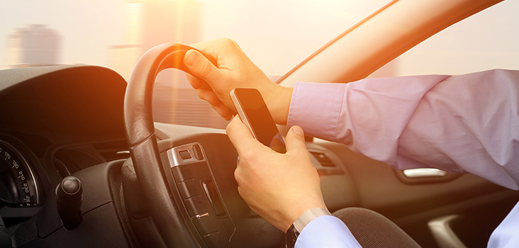 Man driving and playing on phone