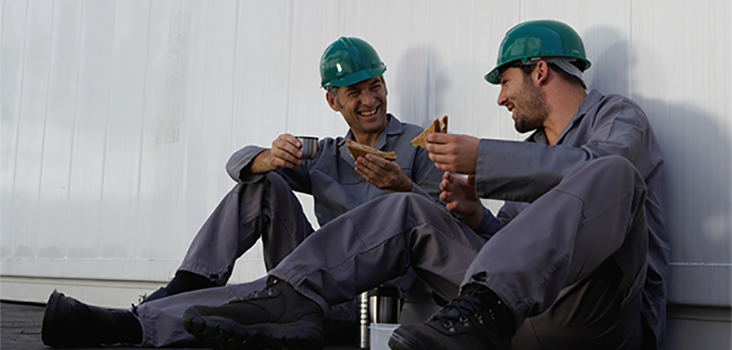 2 workers wearing green hard hats eating lunch and talking