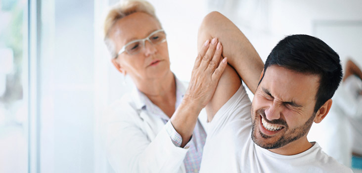 Female physician stretching male's arm as his face is in pain.