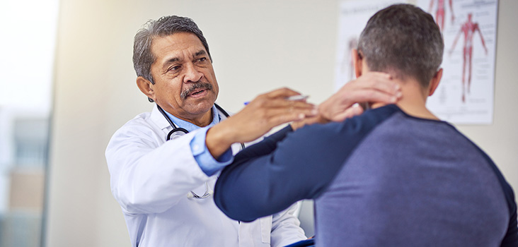 Male physician examines male patient's neck where he feels pain