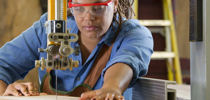 Female carpenter wearing eye gear during drilling to keep her eyes safe.